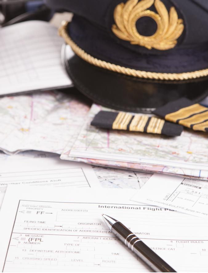 Pilotenmütze liegt auf Flugkarten