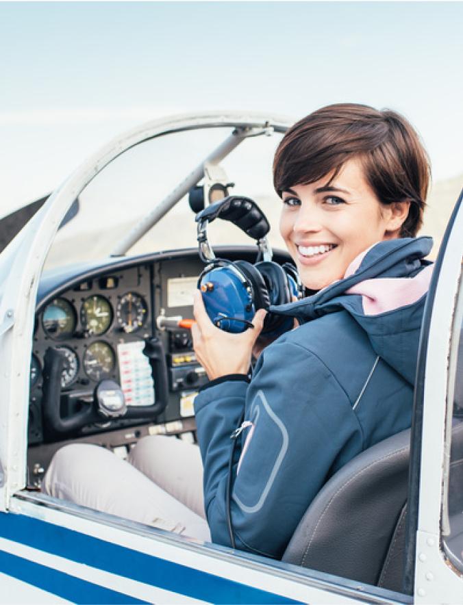 Flugschülerin sitz im Flugzeug und lächelt in die Kamera