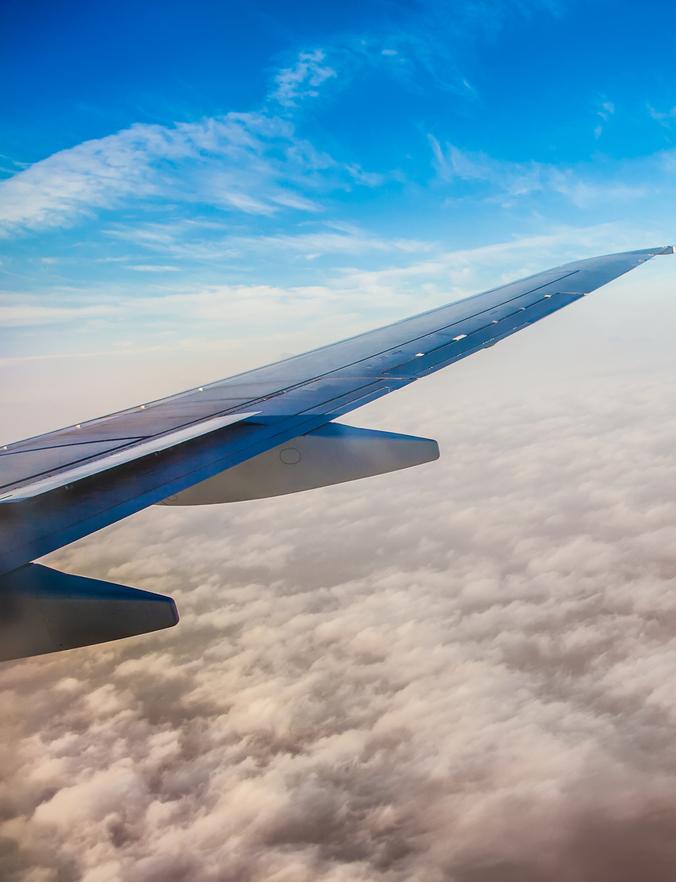 Foto aus dem Flugzeug, zu sehen ist die Tragfläche von hinten, das Flugzeug fliegt