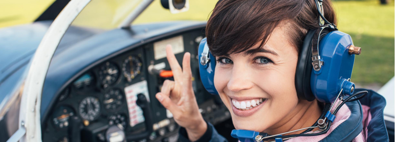 Flugschülering lächelt im Cockpit nach ihrer Flugstunde