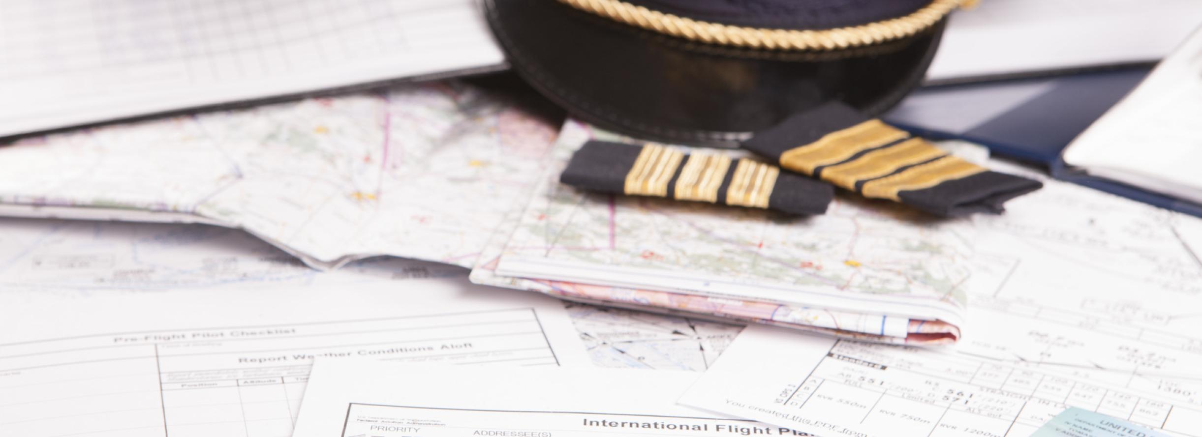 Flugmaterial und teil der Pilotenuniform liegen auf dem Material