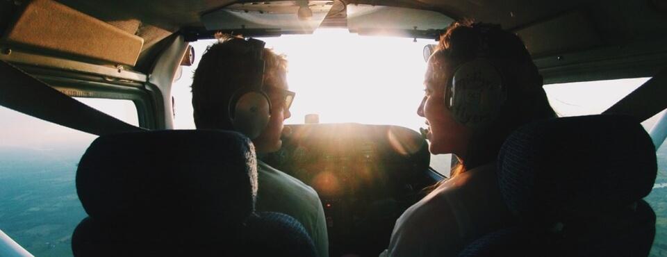 Flugschüler und Fluglehrerin sitzen im Cockpit und lächeln sich an und fliegen dabei in den Sonnenuntergang