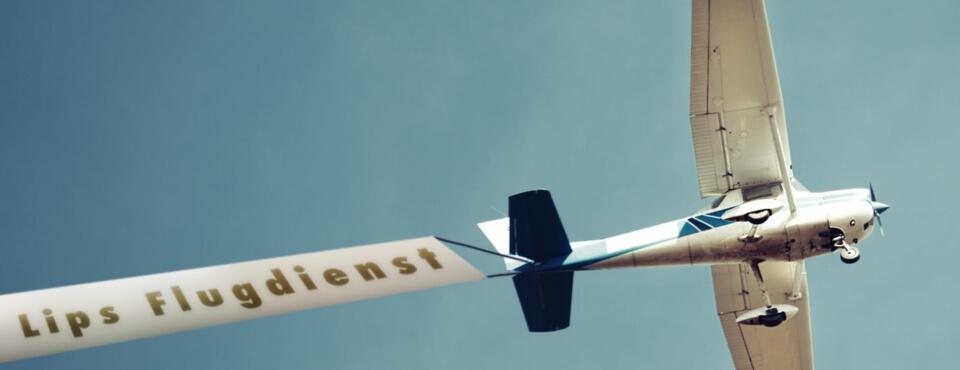 Flugzeug zieht Werbebanner hinter sich her, auf dem Banner steht Lips Flugdienst