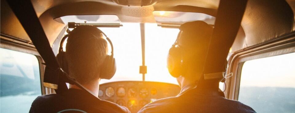 Zwei Piloten im Cockpit fotografiert von hinten wie sie in den Sonnenuntergang fliegen