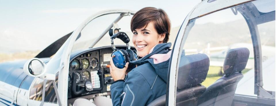 Lächelnde Flugschülerin mit kurzen Haaren und blauer Jacke sitzt im Flugzeug und setzt sich Kopfhörer auf