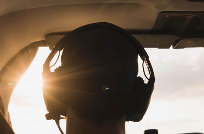 Pilot im Cockpit fliegt in den Sonnenuntergang